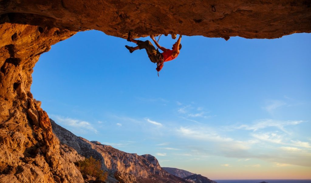 Man Climbing Representing High Performance in Difficult Times
